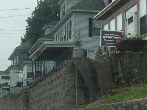 Brown signs stand in front of homes in the Highlands expressing support for a new Lowell High School in the Downtown.